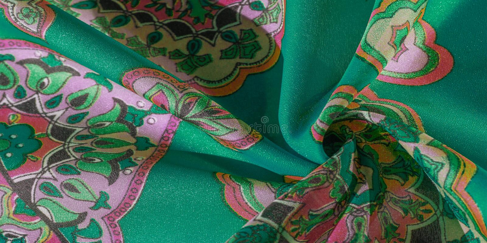 Texture, background, multicolored silk fabric with a pattern of patterns on a green background, jacquard pattern stock photography