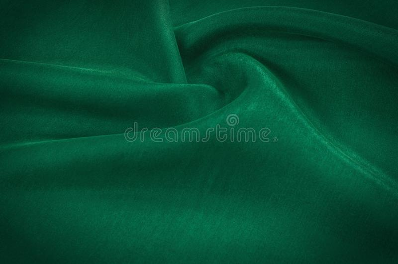 Texture background pattern. Abstract background of luxurious green fabric or liquid waves or wavy folds of a grunge silk texture stock photo