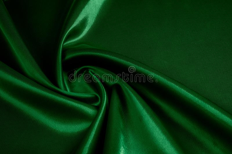 Texture, background, pattern. Texture of green silk fabric. Beau. Tiful emerald green soft silk fabric stock images