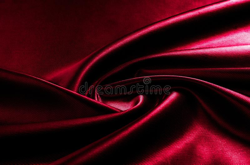 Texture, background, pattern. Red silk fabric.This satin fabric. Is perfect for making fabric flowers for use in hair accessories, jewery making, and fabric royalty free stock image