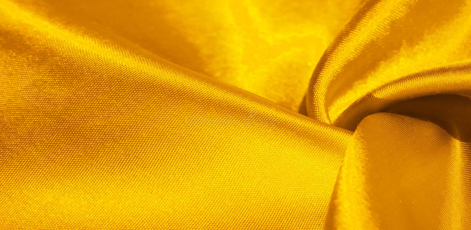 Texture, background, pattern, silk fabric in yellow. This adorable, soft and shiny fabric has a smooth mink surface, perfect for. Creating your projects royalty free stock photo