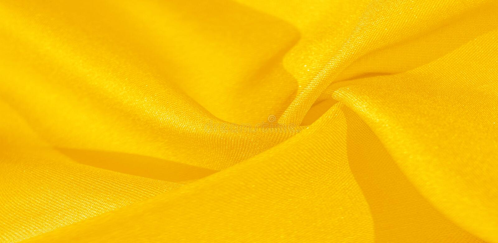 Texture, background, pattern, silk fabric in yellow. This silk is incredibly exquisite. Projects made from this will last a long. Time and will still be in stock photo