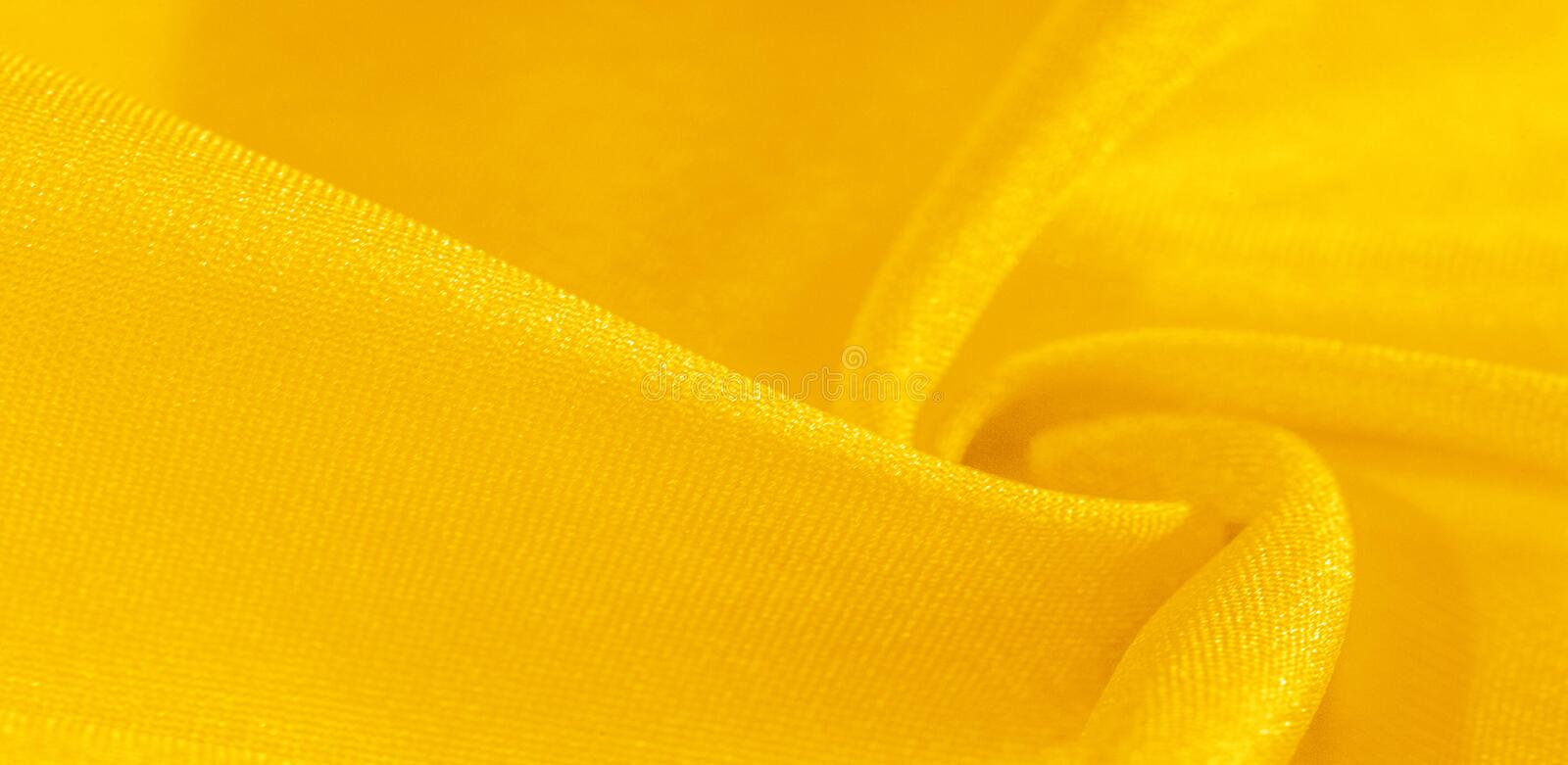 Texture, background, pattern, silk fabric in yellow. This silk is incredibly exquisite. Projects made from this will last a long. Time and will still be in stock photography