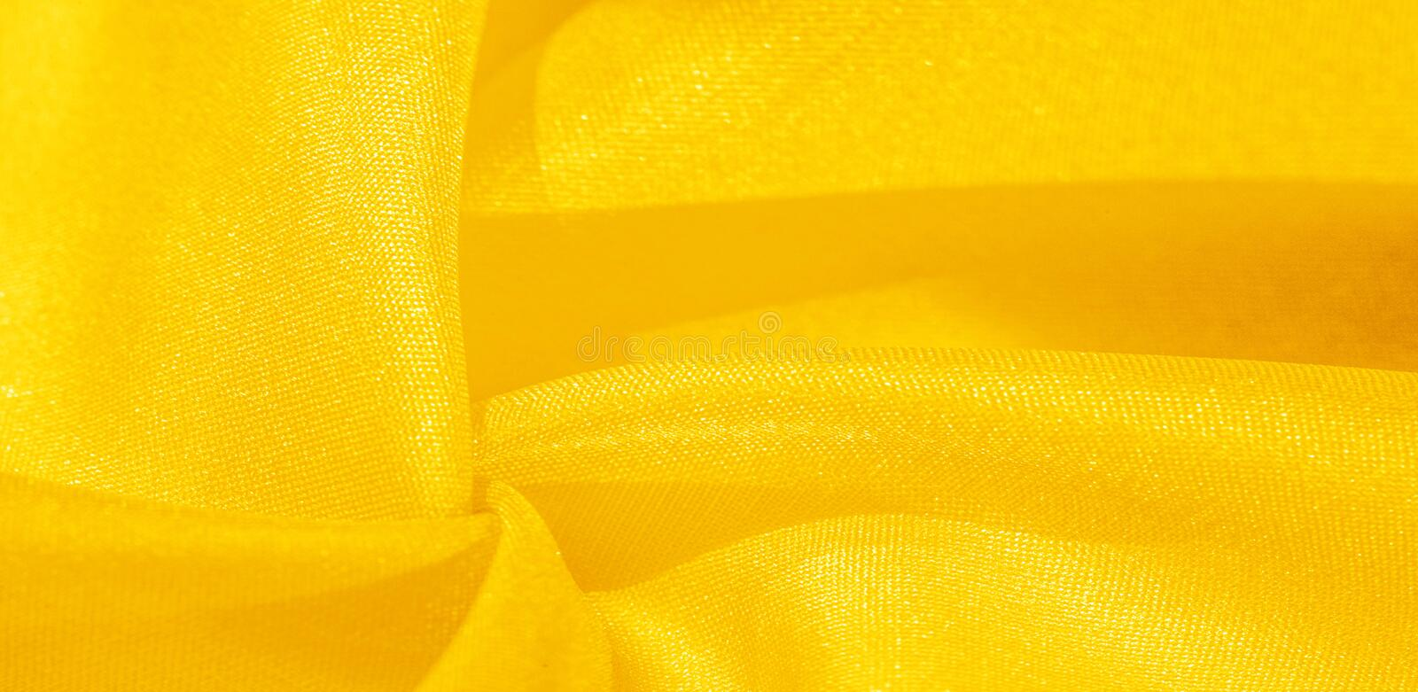 Texture, background, pattern, silk fabric in yellow. This silk is incredibly exquisite. Projects made from this will last a long. Time and will still be in royalty free stock photography