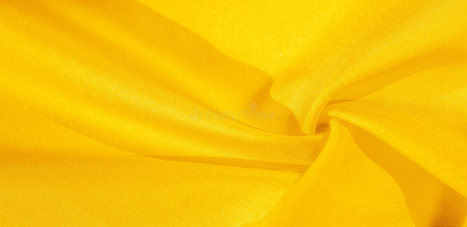 Texture, background, pattern, silk fabric in yellow. This silk is incredibly exquisite. Projects made from this will last a long. Time and will still be in royalty free stock photos