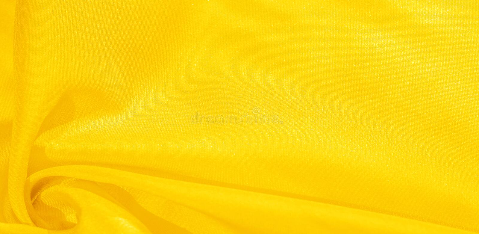 Texture, background, pattern, silk fabric in yellow. This silk is incredibly exquisite. Projects made from this will last a long. Time and will still be in royalty free stock photo