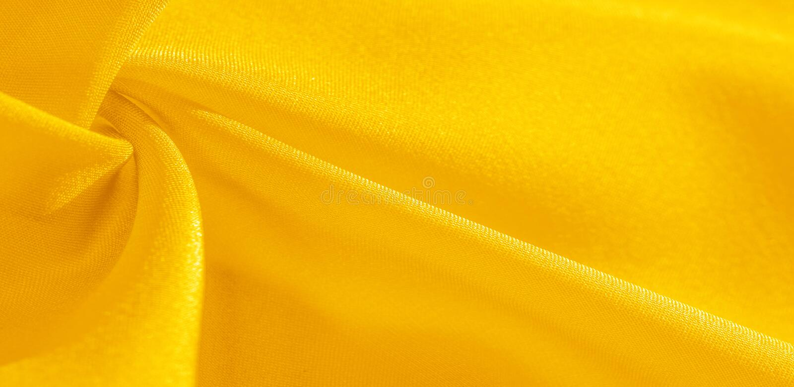 Texture, background, pattern, silk fabric in yellow. This silk is incredibly exquisite. Projects made from this will last a long. Time and will still be in stock image