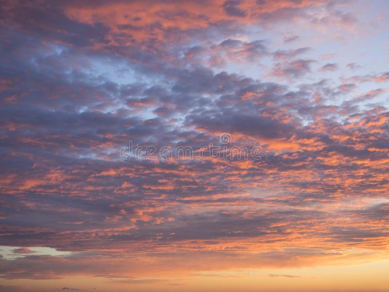 Texture, background, pattern. Sunset or dawn colored tropical clouds, red, pink, blue, orange and yellow pastel colors stock photo
