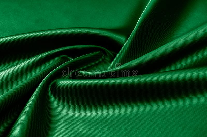 Texture, background, pattern. Texture of green silk fabric. Beau. Tiful emerald green soft silk fabric royalty free stock images