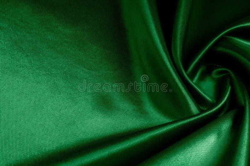 Texture, background, pattern. Texture of green silk fabric. Beau. Tiful emerald green soft silk fabric stock photo