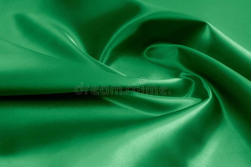 Texture, background, pattern. Texture of green silk fabric. Beau. Tiful emerald green soft silk fabric royalty free stock photos