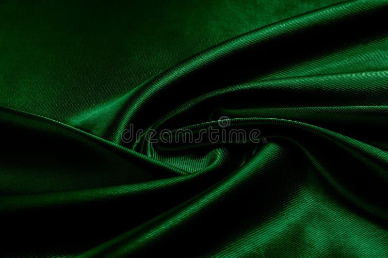 Texture, background, pattern. Texture of green silk fabric. Beau. Tiful emerald green soft silk fabric stock image