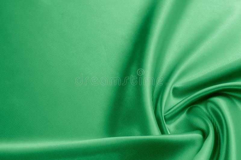 Texture, background, pattern. Texture of green silk fabric. Beau. Tiful emerald green soft silk fabric royalty free stock image