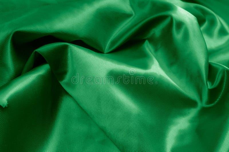 Texture, background, pattern. Texture of green silk fabric. Beau. Tiful emerald green soft silk fabric stock photos
