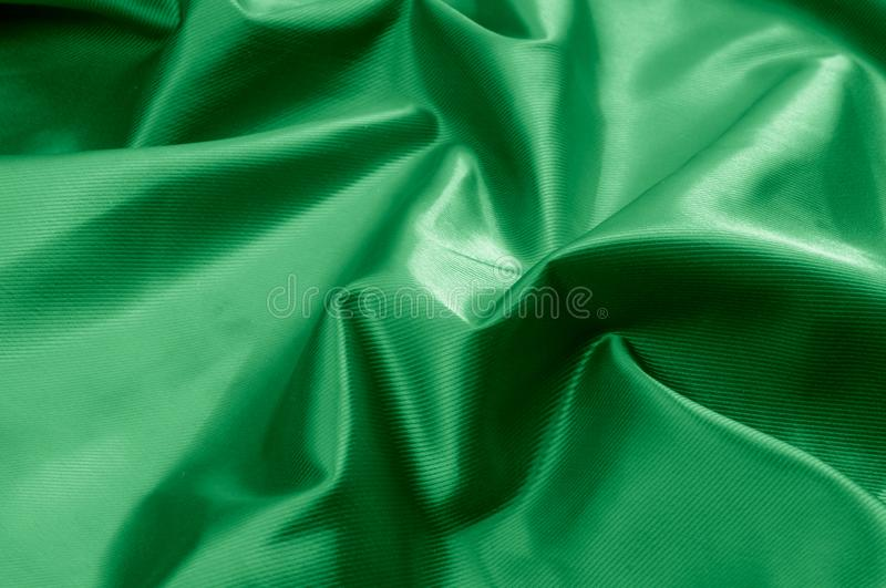 Texture, background, pattern. Texture of green silk fabric. Beau. Tiful emerald green soft silk fabric royalty free stock photography