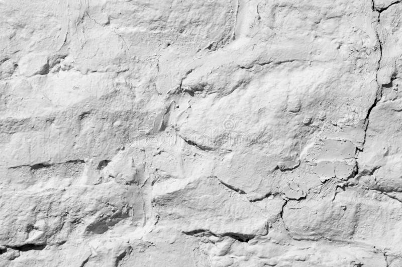 Texture background, pattern. The wall is lined with granite stones and whitewashed with lime. a continuous vertical brick or stone stock image