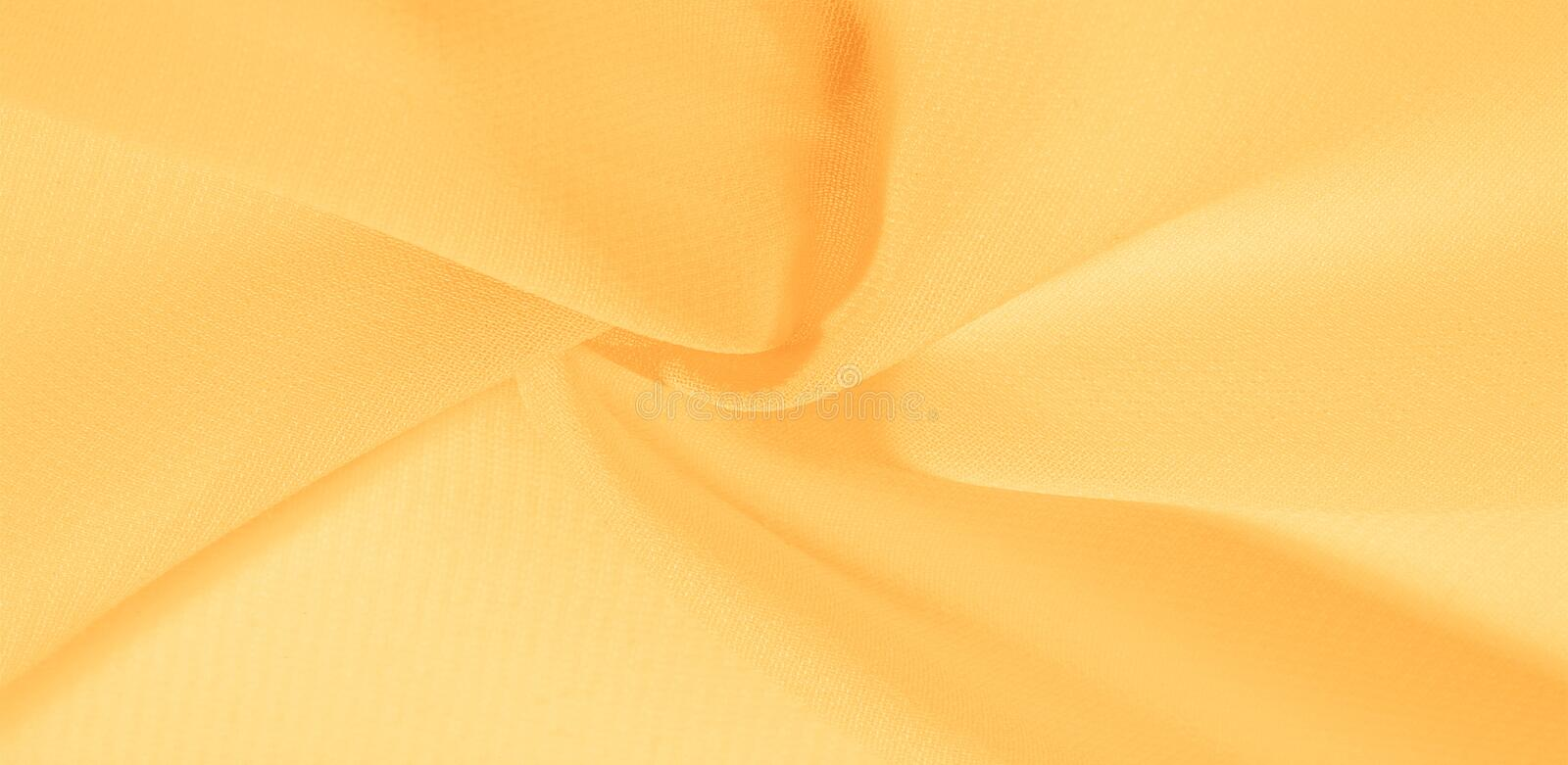 Texture background pattern. Yellow silk fabric with a subtle matte sheen. It is perfect for your design, accents, wallpapers,. Posters and postcards stock photo