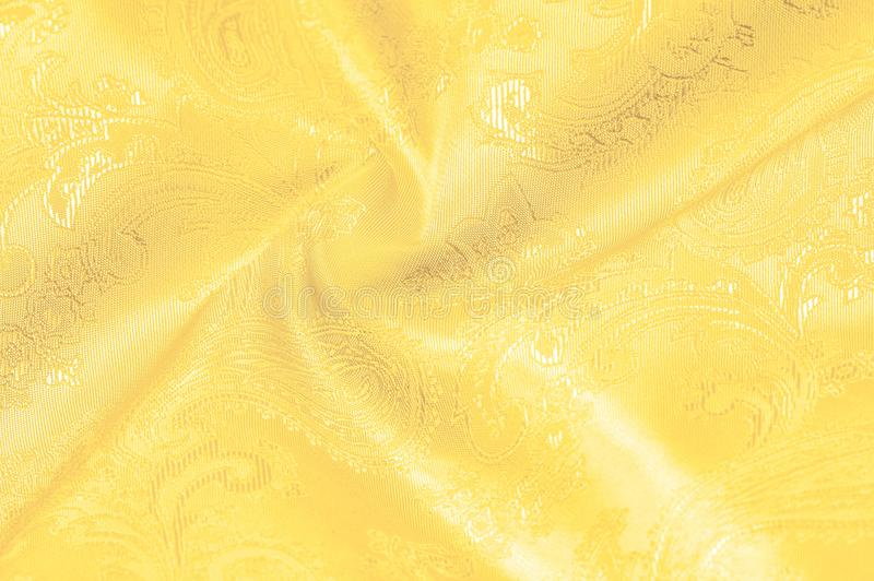 Texture, background, The silk fabric is yellow. This yellow stamping silk crepe de China is here to charge your design! Live. Combination of floral and paisley stock photography