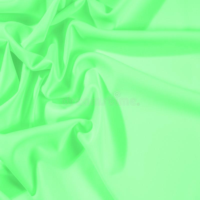 Texture. Background. Template. Cloth - silk green. Known extravagance, this Green silk taffeta is nothing more than a word. Luminous light green fabric is a royalty free stock photo
