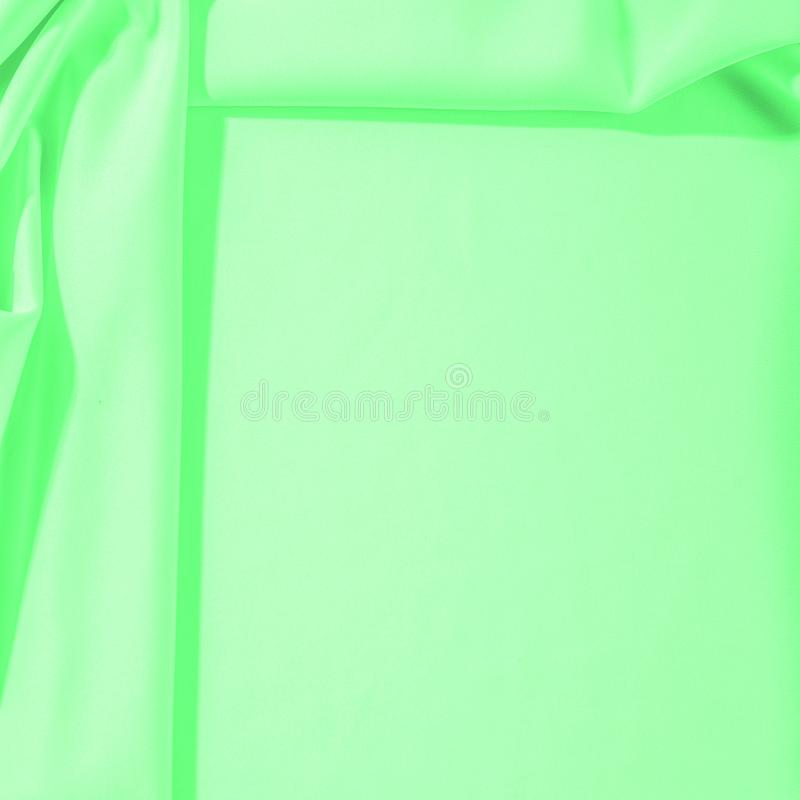 Texture. Background. Template. Cloth - silk green. Known extravagance, this Green silk taffeta is nothing more than a word. Luminous light green fabric is a stock photo