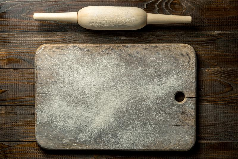Texture on the background, a wooden board in flour, a rolling pin lies next royalty free stock image
