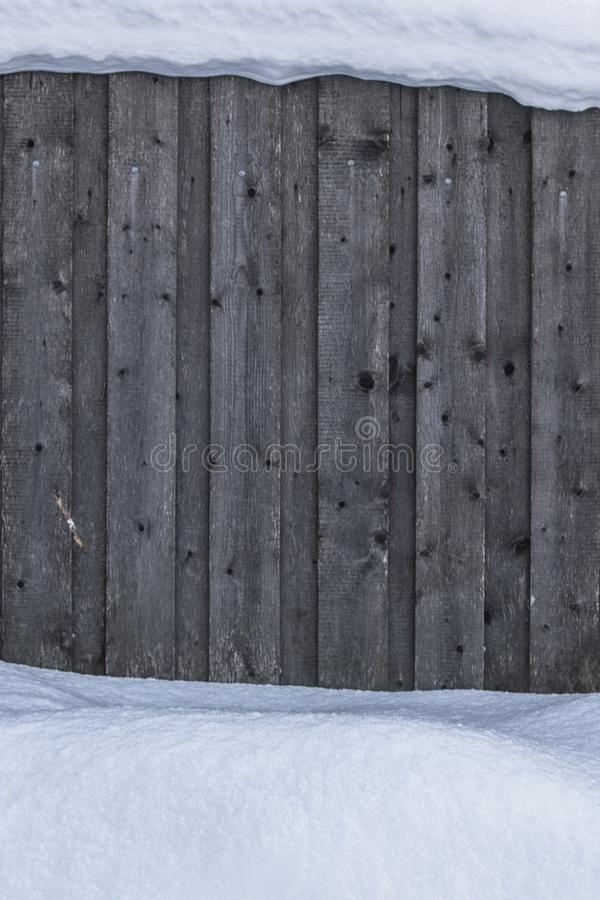 Texture, background. Wooden fence covered with snow from above and below. Wooden fence in the winter. royalty free stock photography