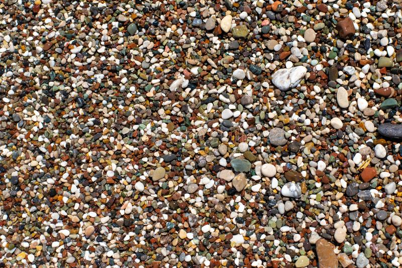 The texture of the beach with coarse sand. The texture of the pebble beach. Background of small pebbles on the beach. Wet pebbles.  stock images