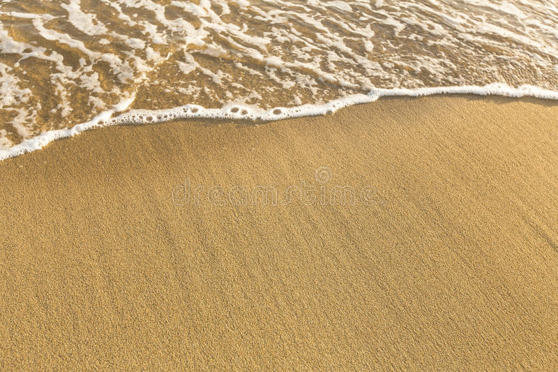 Texture of beach sea sand with a soft wave of surf. Summer. stock photos