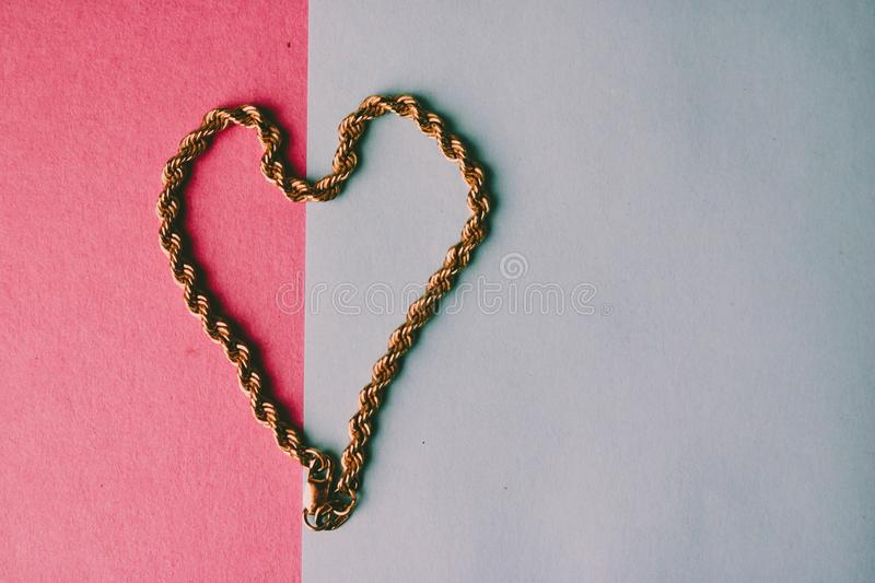 Texture of a beautiful golden festive chain unique weaving in the shape of a heart on a pink purple blue background and copy space royalty free stock photos