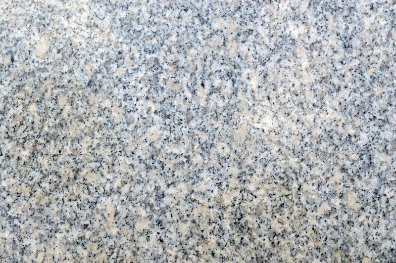 Texture of beige and grey natural granite with polished surface stock photos