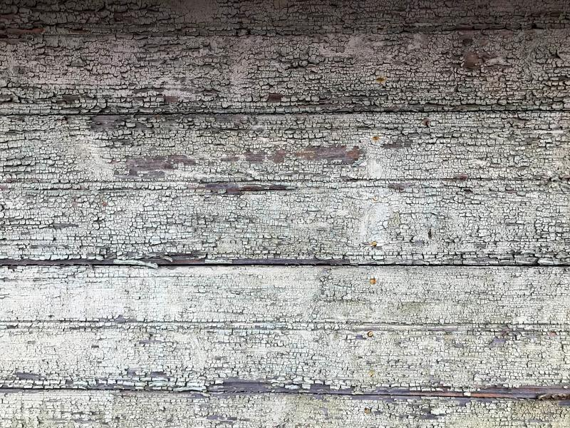 Texture of a black gray old dilapidated wooden wall, a fence with pieces of old shabby exfoliated paint from horizontal worn-out r stock photography