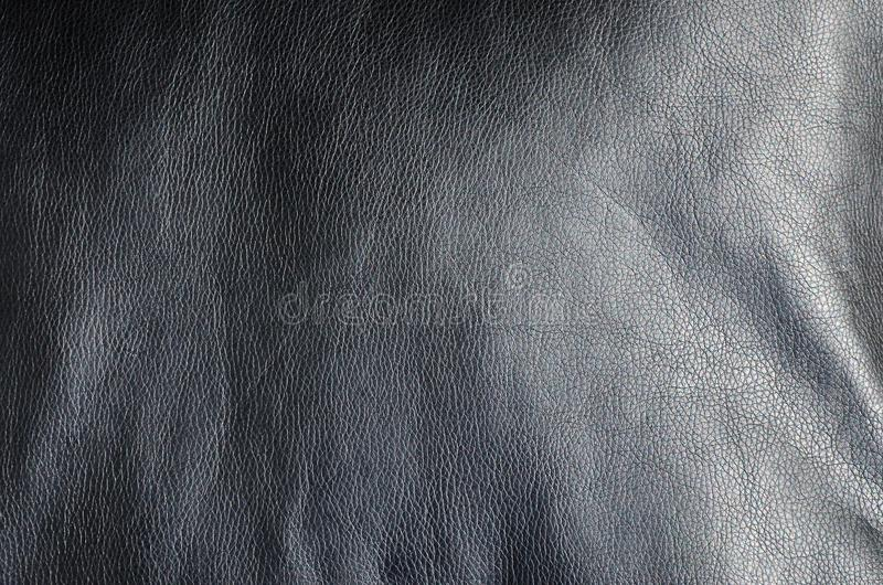 Texture of black leather or dermantin with folds, used as material for women`s and men`s bags, suitcases, pillows for office sofa. S and also for upholstered stock photos