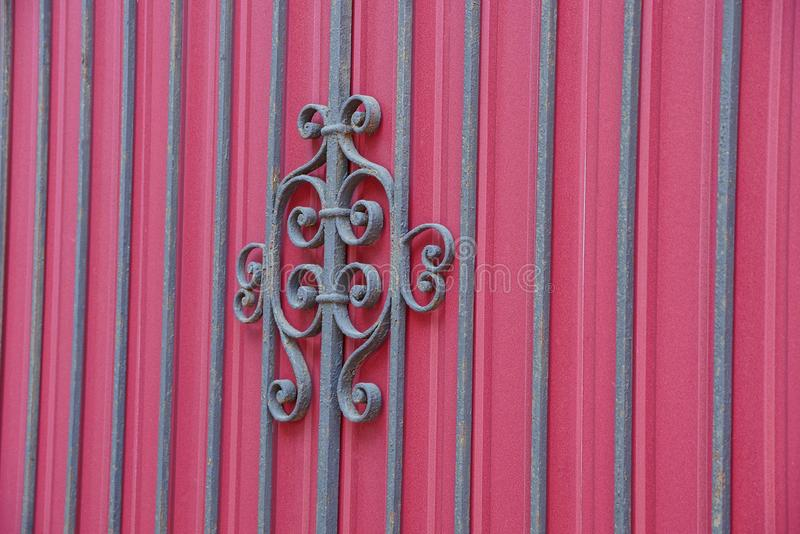 Texture of black steel rods and wrought pattern on a red metal wall. Texture of black steel rods and forged pattern on a fragment of a red metal wall stock images