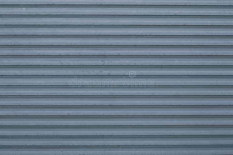 Texture of blue and gray corrugated metallic surface. Blue ribbed background with stripes, straight lines. Modern pattern of blue royalty free stock images