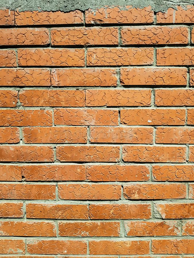 The texture of a brick wall with orange color.The brick has a form of appliances on it .. stock photo