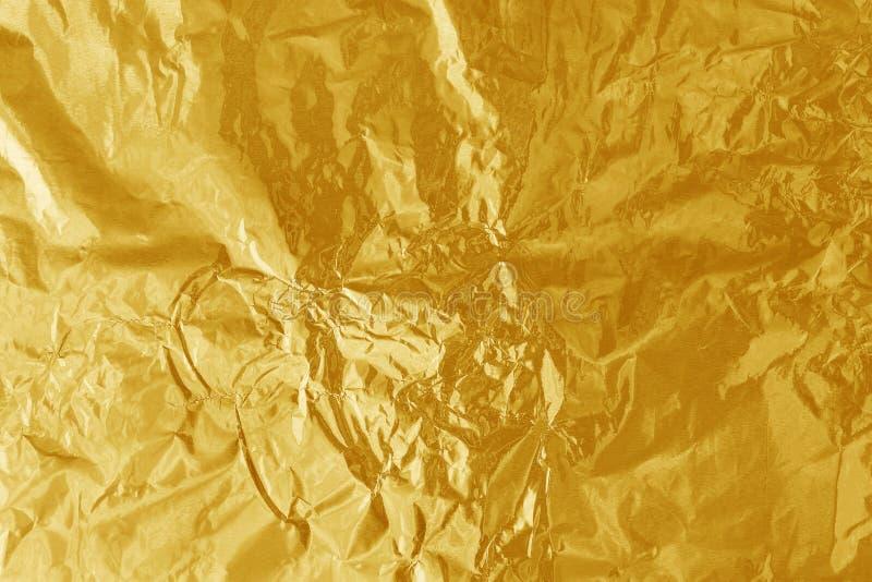 Texture brillante de feuille de feuille d'or, papier d'emballage jaune abstrait pour le fond photos stock