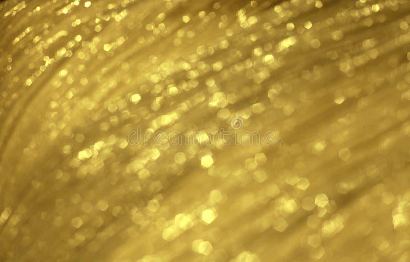 Texture brouillée de fête d'or brillante de tissu Contexte rougeoyant abstrait photos stock