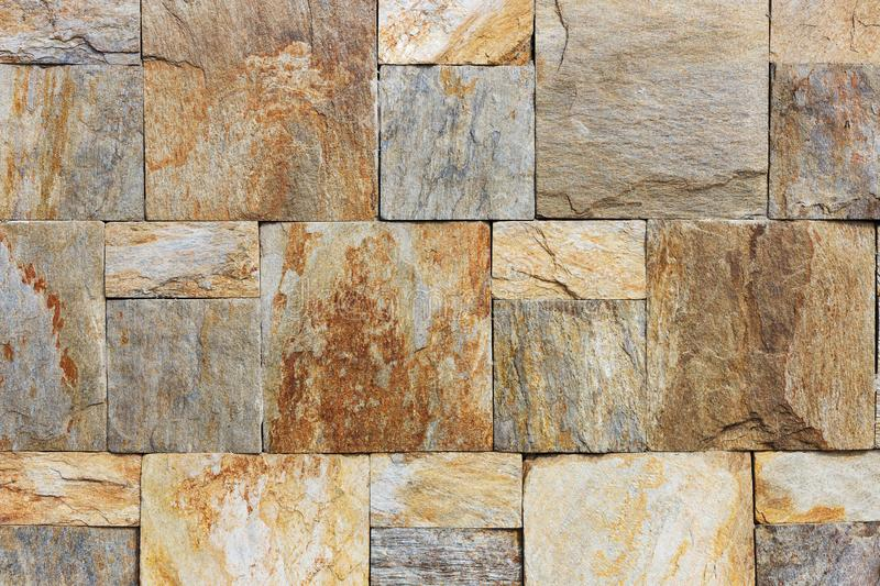 Texture of the brown and grey wall made of square stone tile bricks.  royalty free stock image