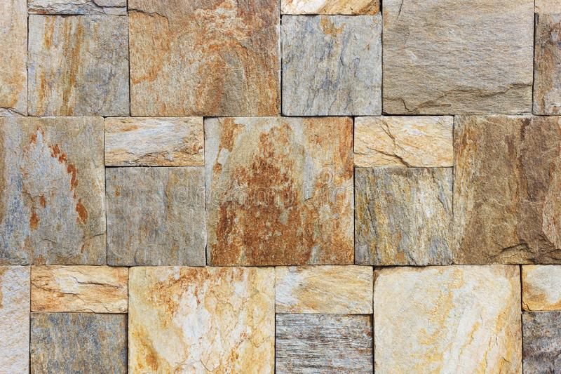 Texture of the brown and grey wall made of square stone tile bricks.  royalty free stock images