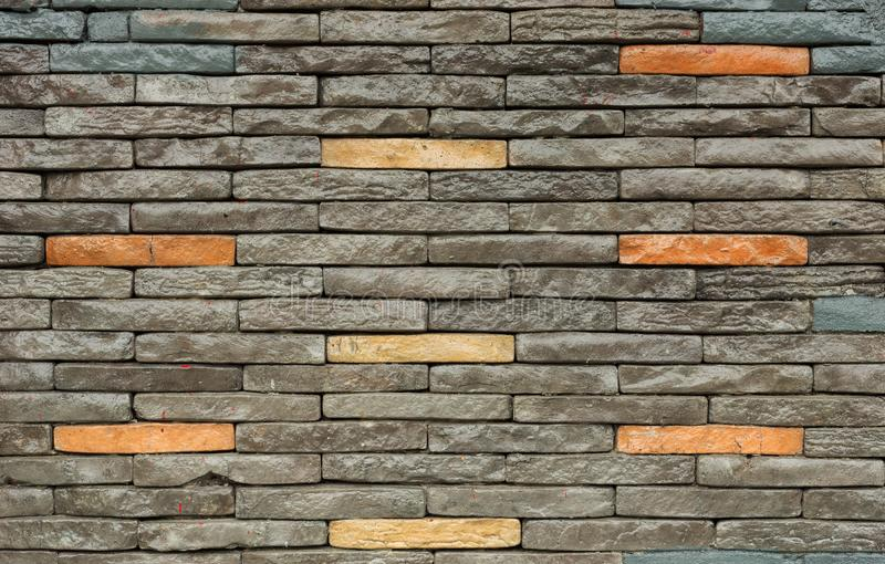 Texture of the brown and grey wall made of stone tile bricks.  royalty free stock photography
