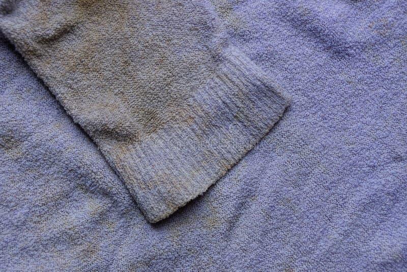 Texture brune lilas de tissu de vieux vêtements souillés avec des douilles image stock