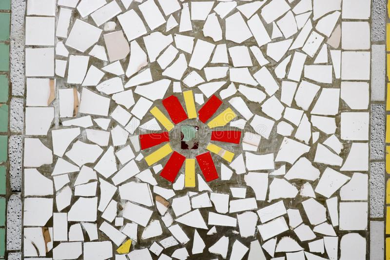 Texture of a ceramic mosaic of glass fragments of various colors with a flower pattern. The background.  stock image