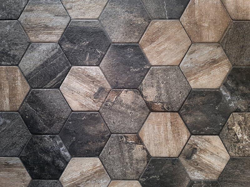 The texture of the ceramic tiles in the form of a hexagon made of brown natural stone Struttura del concetto, sfondo fotografia stock