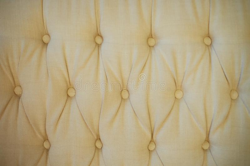 Texture,classic sofa upholstery with light fabric buttons. royalty free stock photos