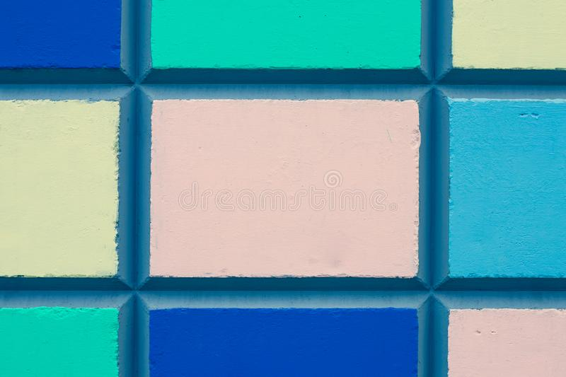 Texture of a colorful mosaic of concrete slabs. Abstract pattern of multicolored squares on a concrete wall. Colorful painted bloc royalty free stock photos