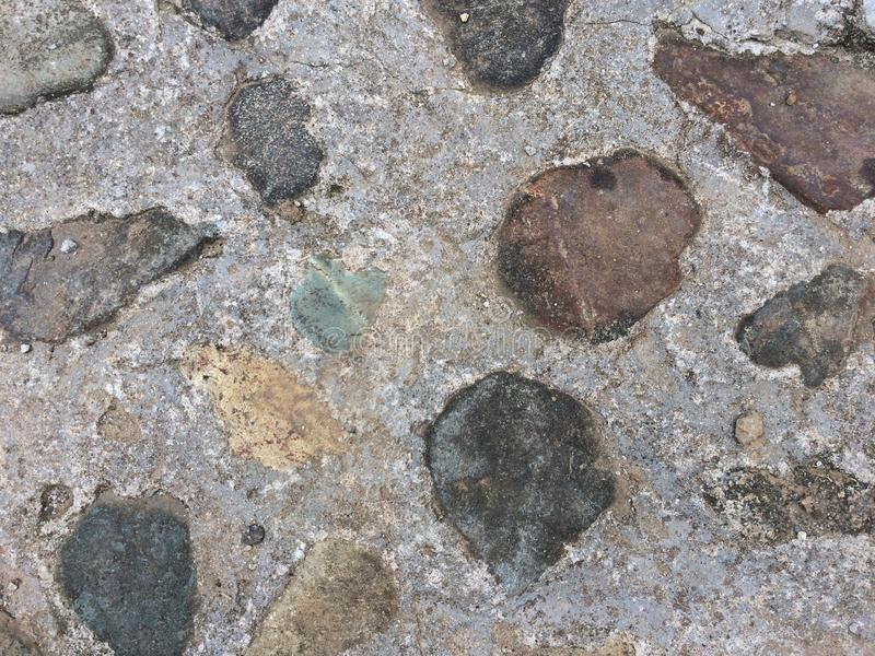Texture of a country walker. Abstract created with buried rocks in concrete, it is possible to recreate a series of abtracts that denote uniform textures in royalty free stock photography