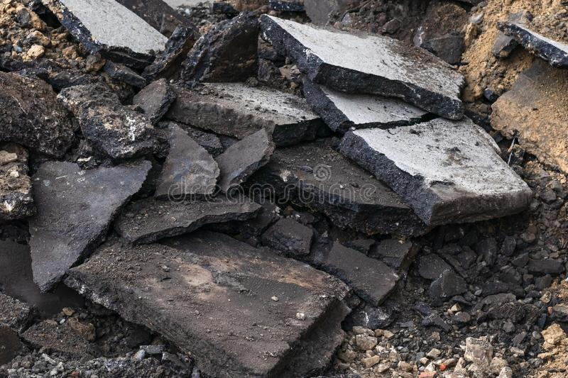 Texture of cracked asphalt. Concrete replacement outdoors. City maintenance. Black structure. Pile of plates. Construction garbage royalty free stock image
