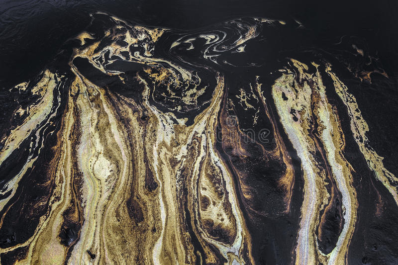 Oil spill texture on the sand beach. Texture of Crude oil spill on sand beach from oil spill accident royalty free stock image
