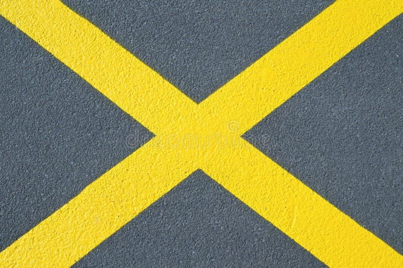 Texture d'asphalte avec la croix jaune photos stock