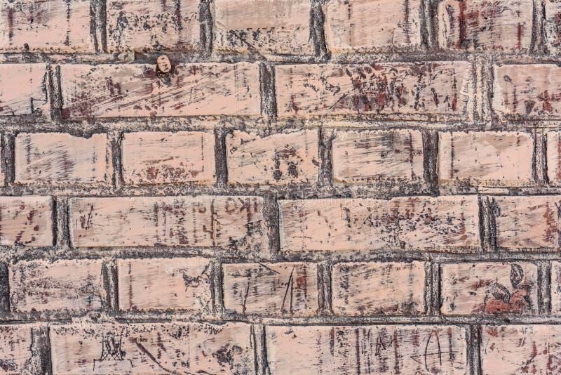 Texture d'un mur de briques avec les fissures et les éraflures qui peuvent être employées comme fond image libre de droits